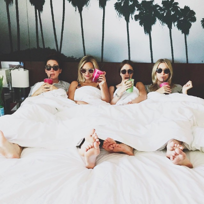 bachelorette party sipping drinks in bed