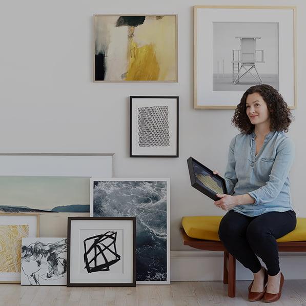 Woman sitting next to art wall