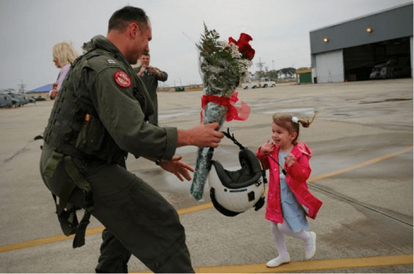 Little girl greeting solider with flowers