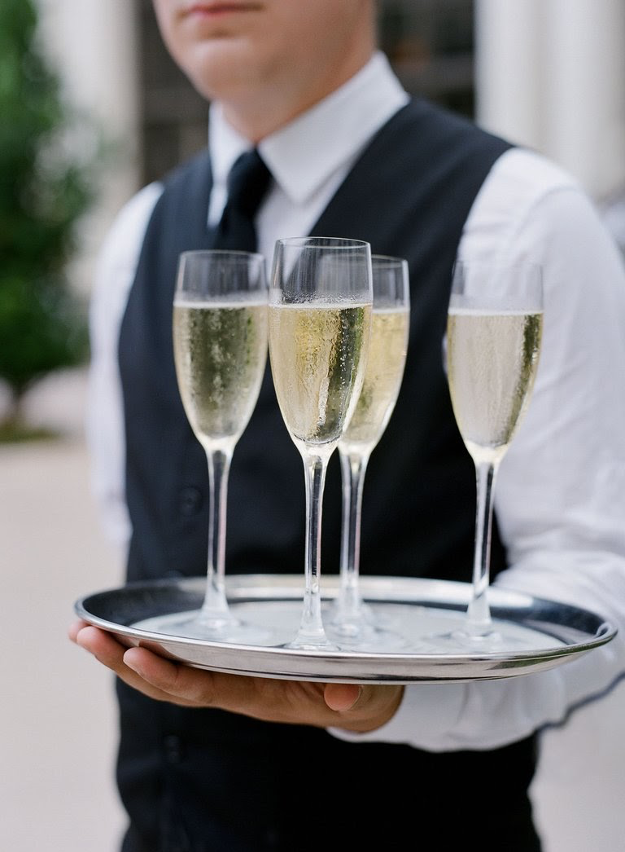 waiter holding champagne glasses
