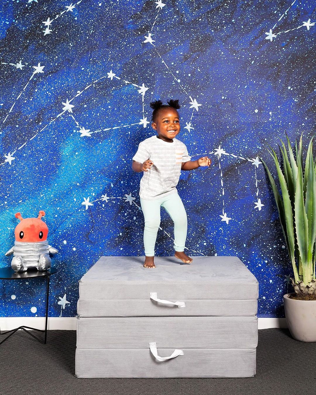 Little girl smiling in front of space painting