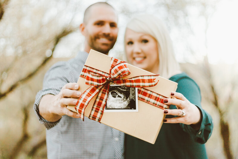 Couple holding present with baby photo