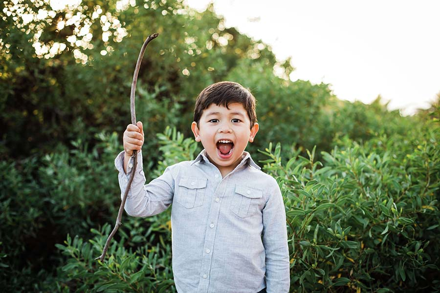 Kid holding stick outdoors