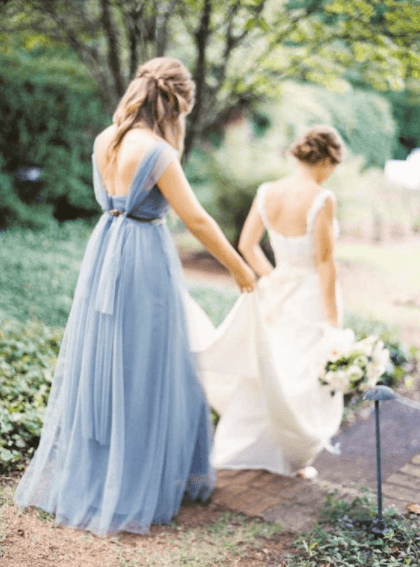 maid of honor holding bride's dress