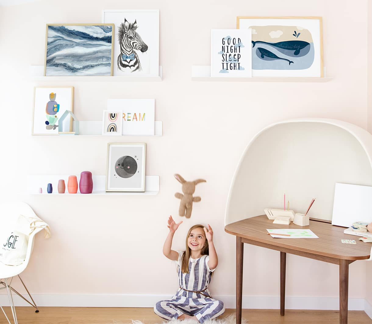 child playing with stuffed animal beside art gallery wall