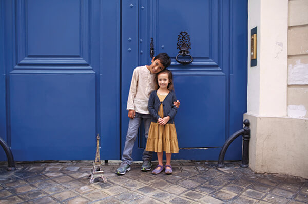 Kid standing in front of blue door