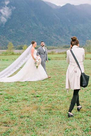 wedding photographer taking picture of couple outdoors