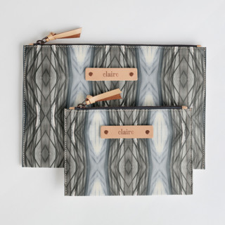 This is a brown zipper pouch by Angela Simeone called Ikat Stripe.