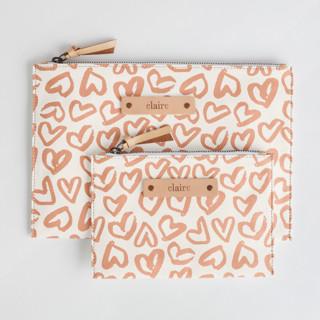 This is a pink zipper pouch by Ariel Rutland called Heart Flutter in standard.