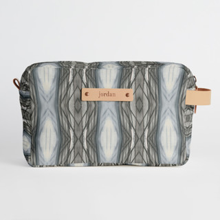 This is a brown dopp kit by Angela Simeone called Ikat Stripe in standard.