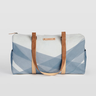 This is a blue duffle bag by Roopali called Crisscross in standard.
