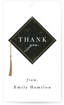 This is a black graduation tag by Caitlin Considine called Proudest Moment with standard printing on signature in sticker.