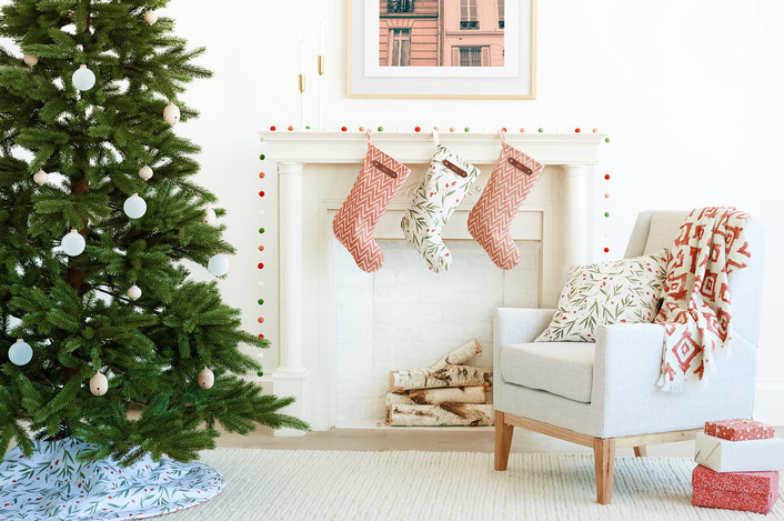 .Simple peaceful Christmas decor in white living room with linen chair and soft reds