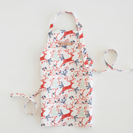 This is a colorful kids apron by Phrosne Ras called Jumping Reindeer.