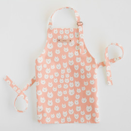 This is a pink kids apron by Milk and Marrow called Kitty Power in standard.