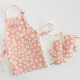 This is a pink kids apron by Milk and Marrow called Kitty Power.