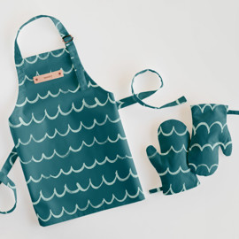 This is a blue kids apron by Shirley Lin Schneider called Surf's Up.