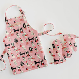 This is a pink kids apron by Vivian Yiwing called Christmas Dogs.