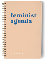This is a brown journal by Erika Firm called Feminist Agenda with standard printing on premium cover stock in notebook.