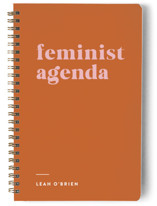 This is a orange journal by Erika Firm called Feminist Agenda with standard printing on premium cover stock in notebook.