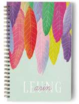 This is a colorful journal by Baumbirdy called Feather Wild One with standard printing on premium cover stock in notebook.