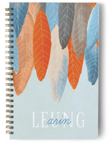 This is a blue journal by Baumbirdy called Feather Wild One with standard printing on premium cover stock in notebook.