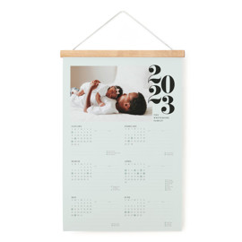 This is a blue hanging bar calendar by Jennifer Lew called Stacked Year with standard printing on signature in one-page calendar.