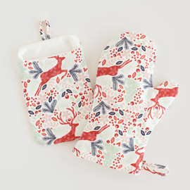 This is a red apron by Phrosne Ras called Jumping Reindeer.