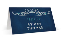 This is a blue wedding place card by GeekInk Design called Ornate Deco with gloss-press printing on signature in placecard.