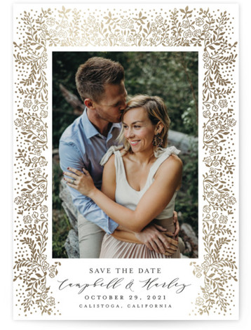 This is a portrait botanical, white Save the Dates by Chris Griffith called Unchained Melody with Foil Pressed printing on Signature in Classic Flat Card format. A delicate and intricate floral foil design framing your couple's photo