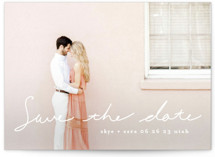This is a white save the date by Phrosne Ras called plain handwritten with standard printing on signature in standard.