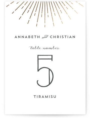 This is a portrait vintage, gold Table Numbers by Dulce Dahlia called Vintage Radiance with Foil Pressed printing on Signature in Classic fold over (blank inside) format. An elegant vintage wedding invitation with a pretty sunburst frame.