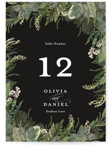 This is a botanical, black Table Numbers by Susan Moyal called Side Swept with Standard printing on Signature in Classic fold over (blank inside) format. Greenery, leaves, and vines sweep around the wedding details
